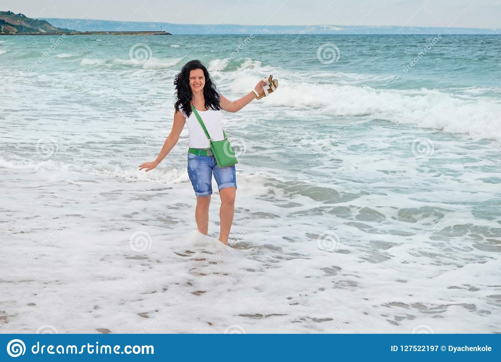 A young long-haired girl stands among the waves in the sea. white sea foam on the shore of the Black Sea in Bulgaria