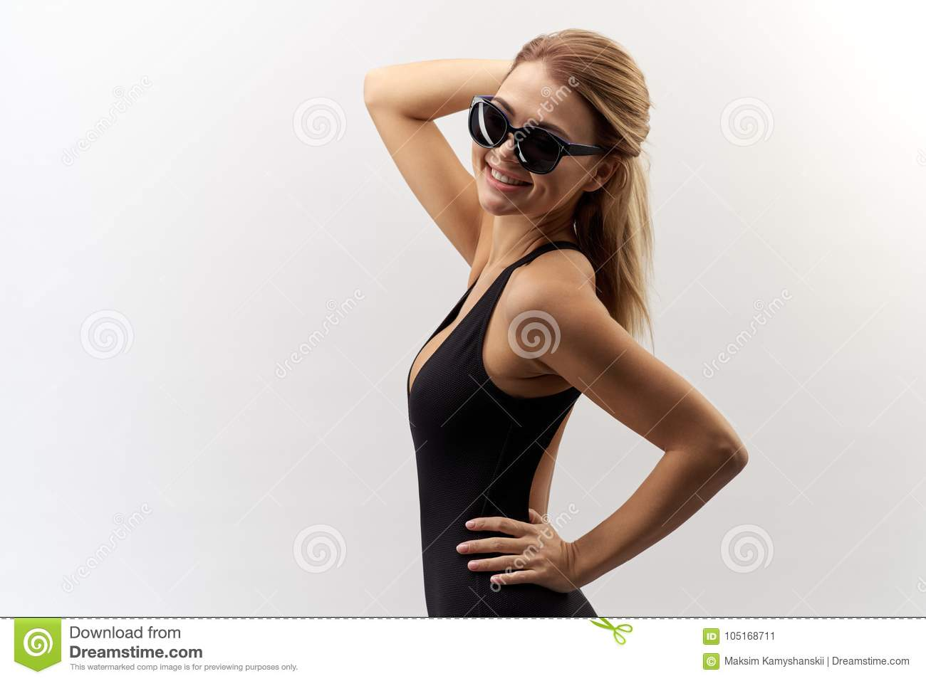 2cd61dee13d Young long-haired white-skinned girl in a black bathing suit and sun  glasses with a smile, posing for contrast Studio portrait on isolated white  background