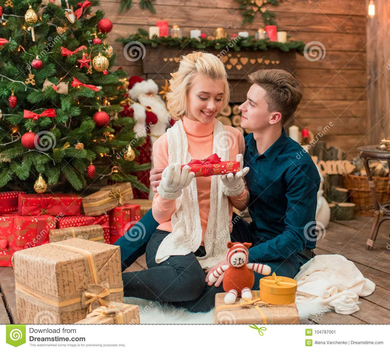 Young Loving Christmas Couple Opening A Present Together Stock Image