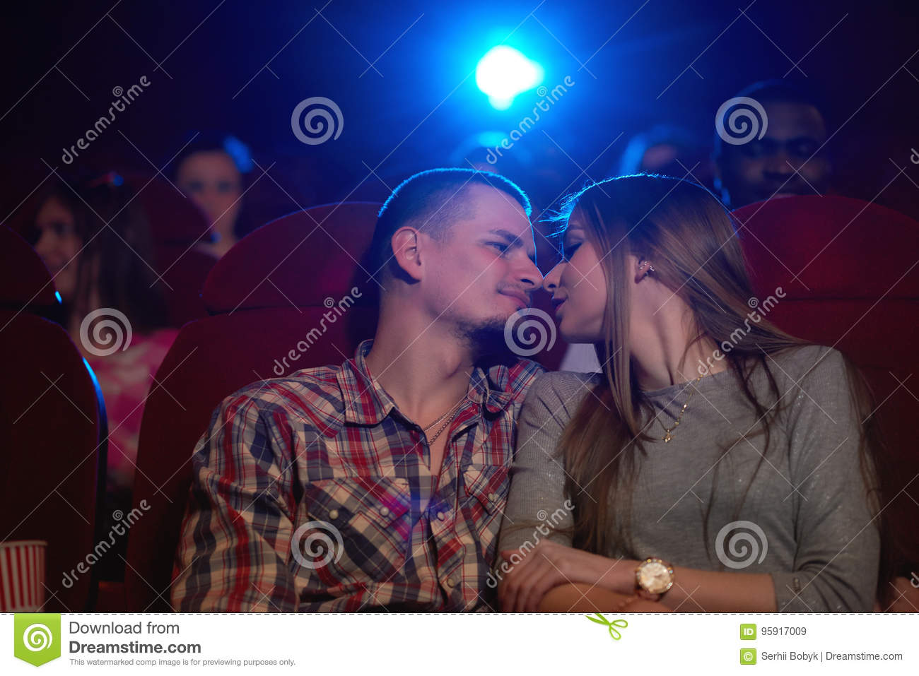 Young Loving Couple Sharing Romantic Moment At The Cinema Stock