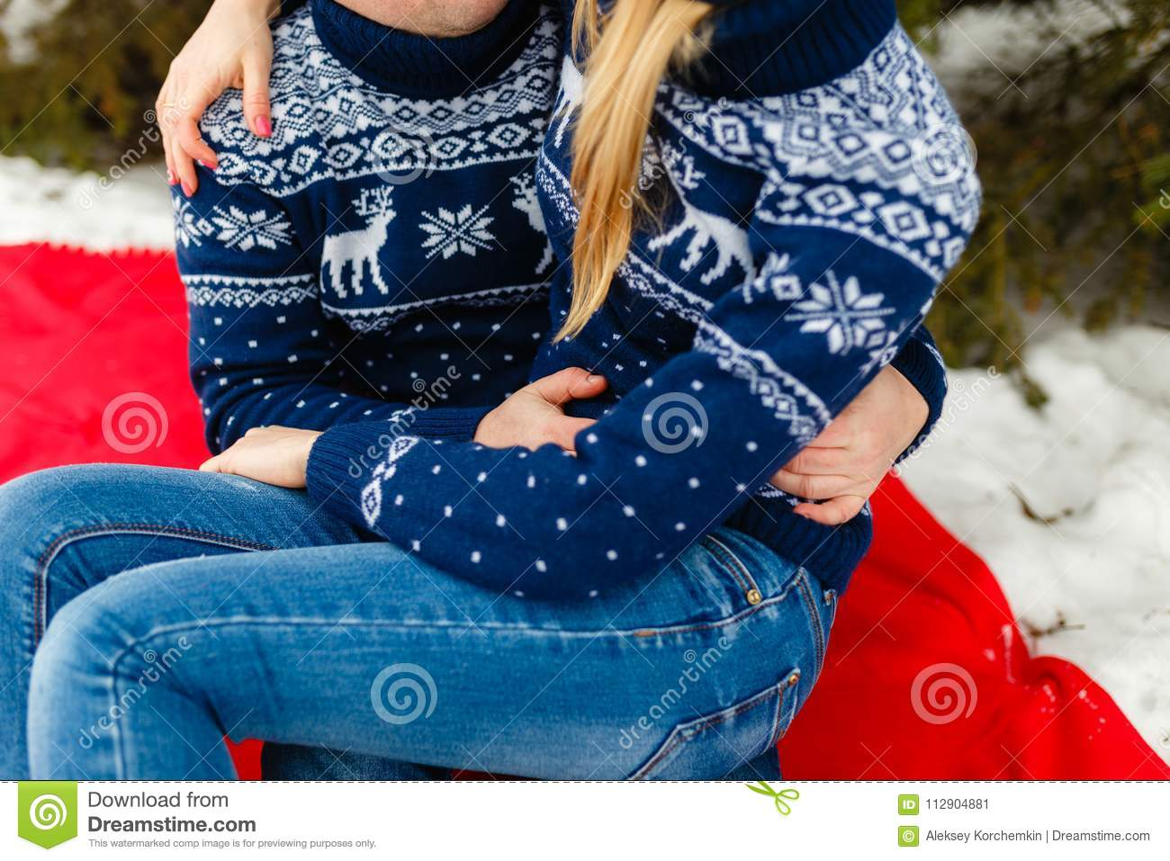 Young Loving Couple Warm Sweaters And Jeans Hugging Sitting On A
