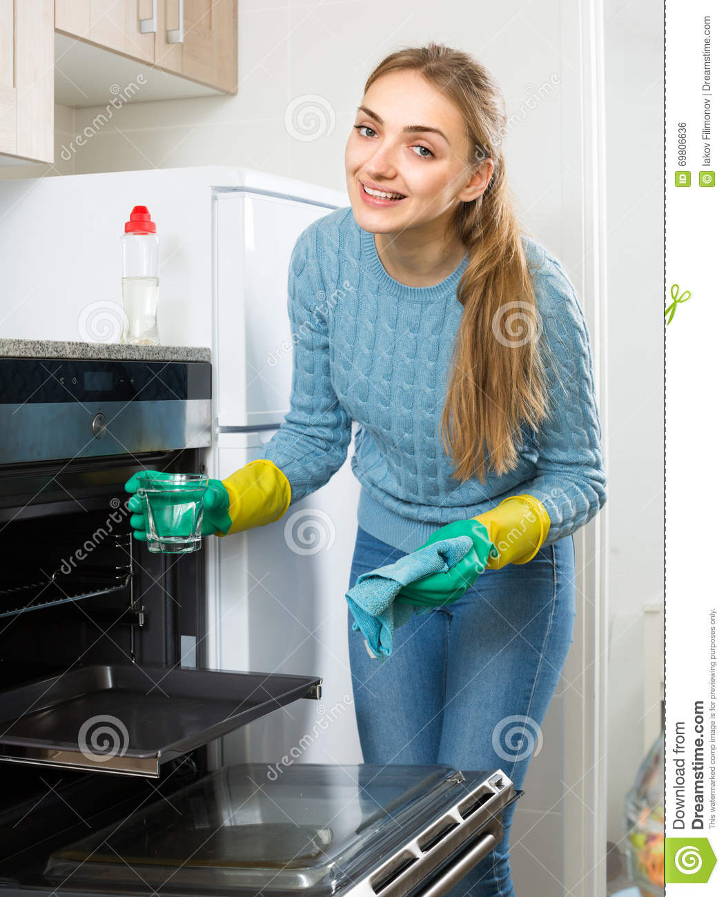 Young Maid Doing Oven Clean-up Stock Photo - Image of kitchen, maid ...