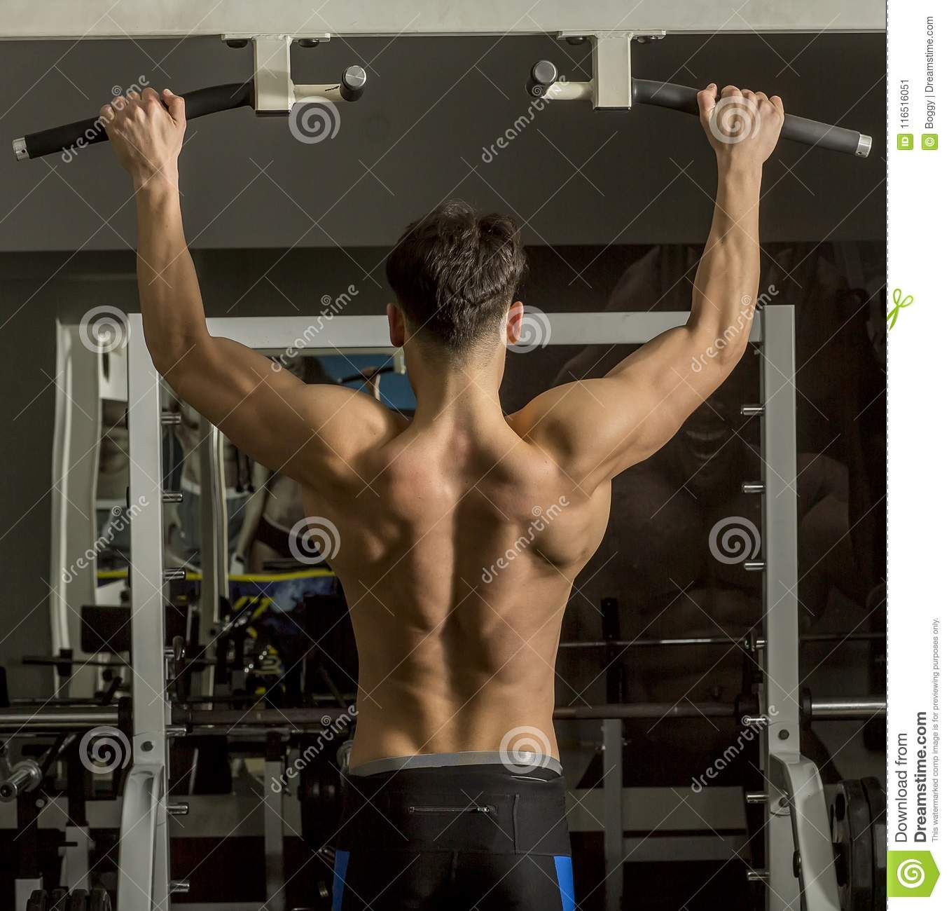 Young Male Adults Doing Pull Ups In The Gym Stock Image