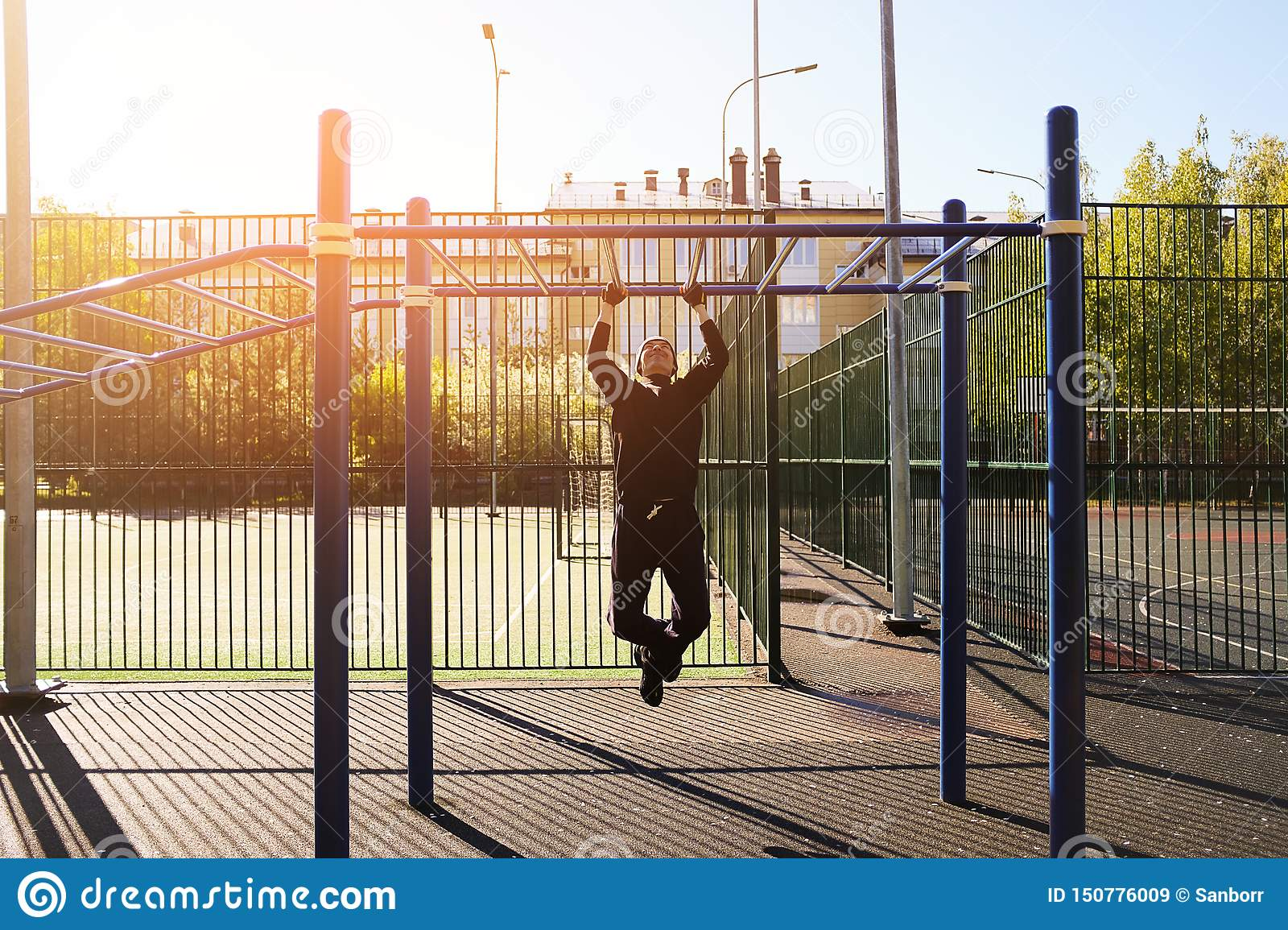 A young male athlete does pull-UPS exercises on a horizontal bar, on a sports ground, outdoors, at dawn or on a Sunny day. The