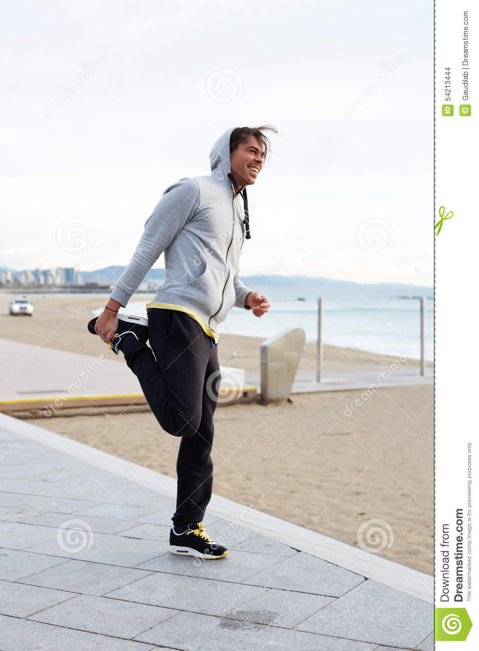 Young male athlete warming up after an intense running on the beach
