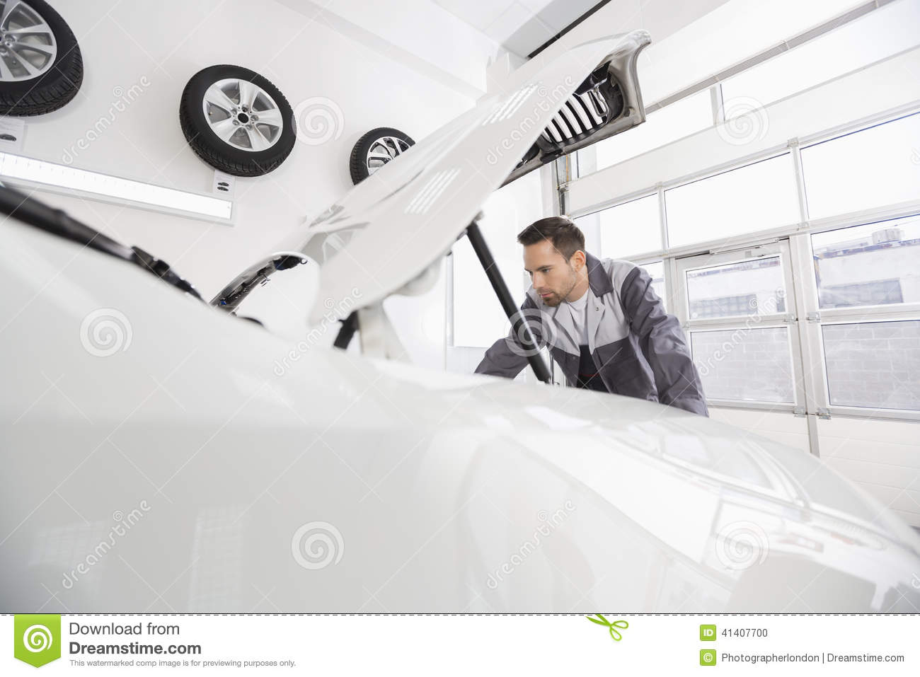 Young male automobile mechanic examining car engine in repair shop