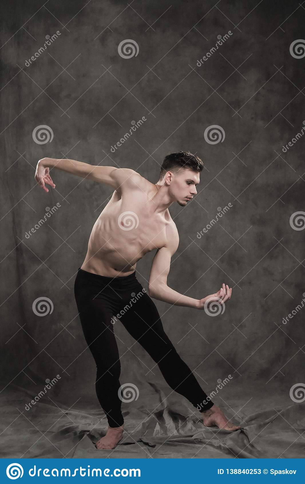 5ecf9e7b94da7 A young male ballet dancer with black leggings and a naked torso performs  dance moves against