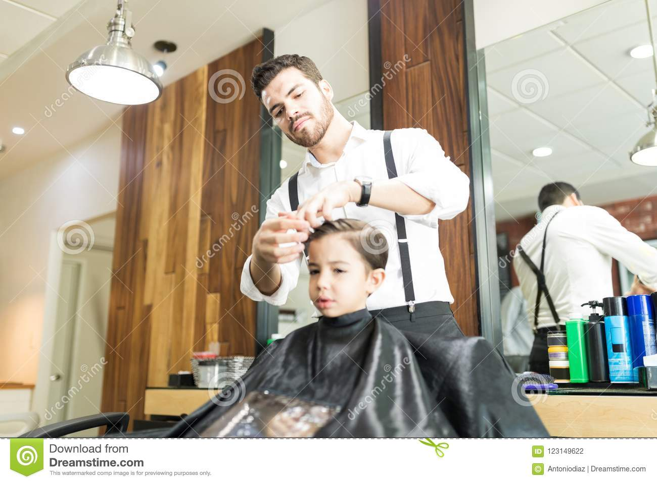 Young Barber Styling Boys Hair After Haircut In Shop Stock Photo