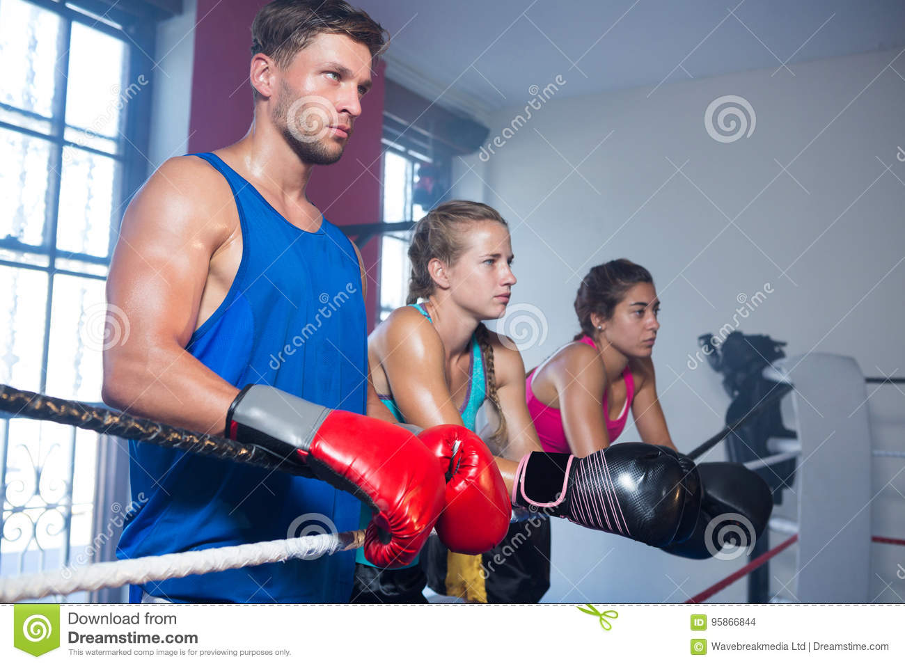 Young male boxer standing by female athletes