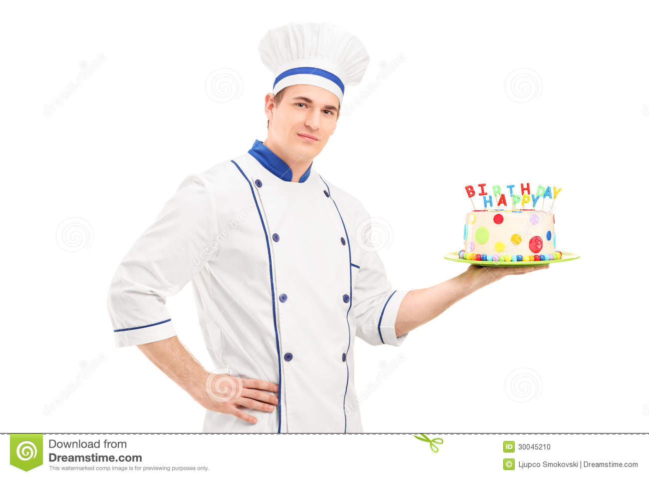 Young male chef in a uniform holding a decorated birthday cake