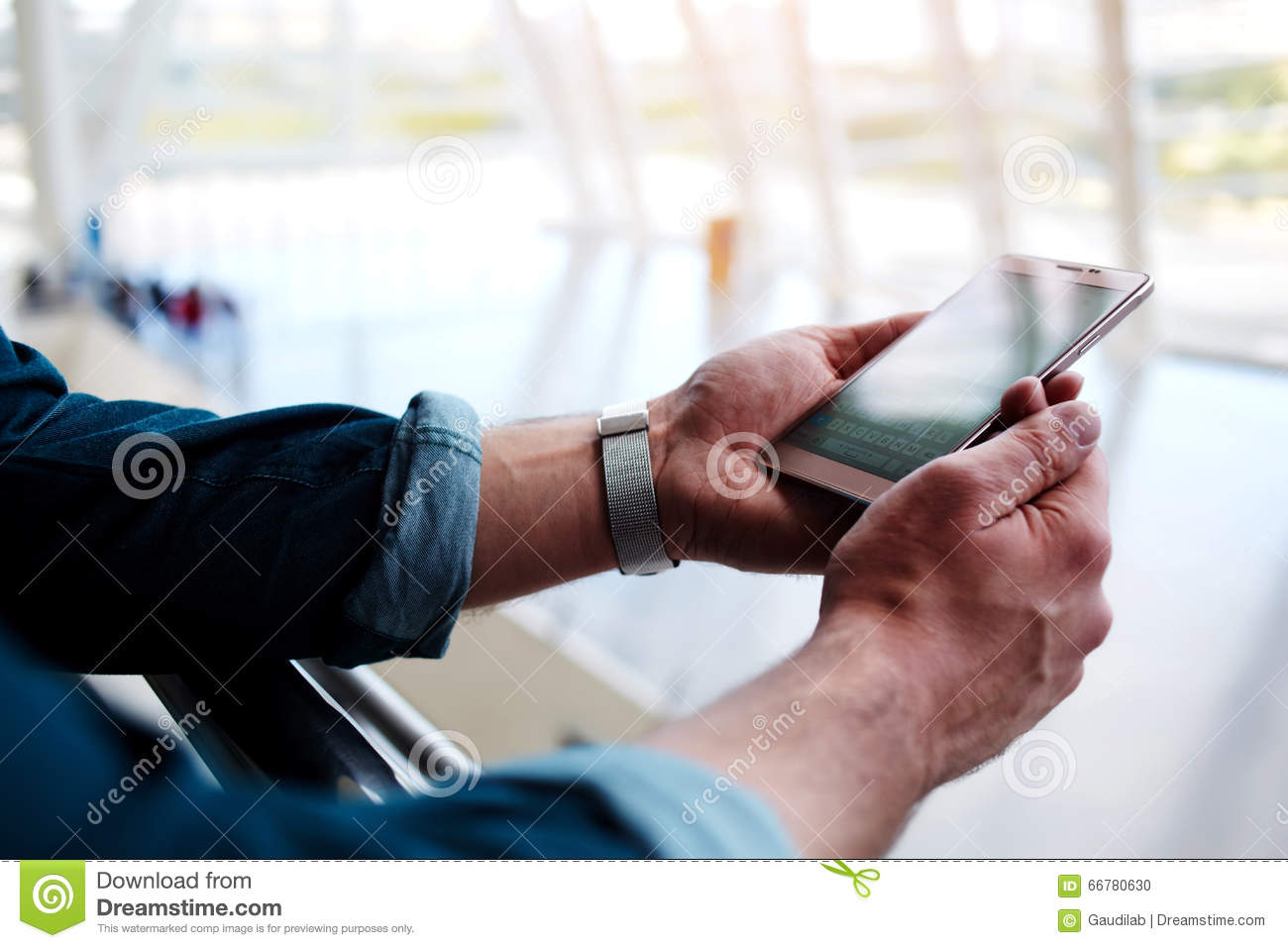 Young Male Connecting To Wireless Via Mobile Phone While Waiting For