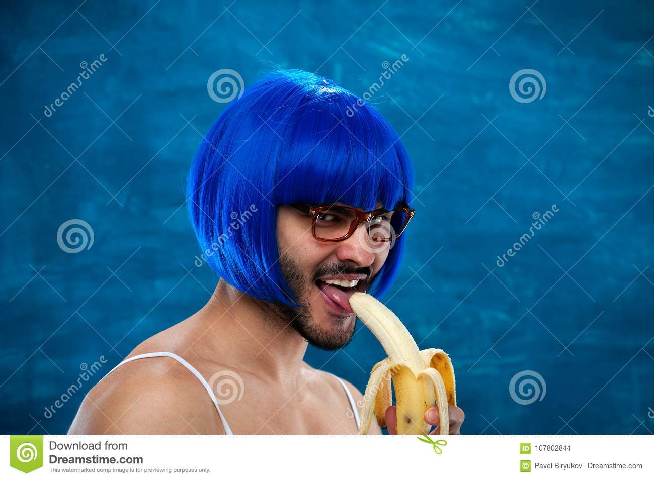 Sensual young male cross dressing person wearing blue wig and female cloth  eats banana. Place for text. 685d65796