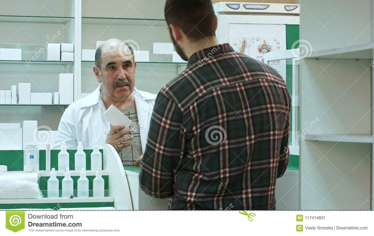 Young male customer getting blister of pills from pharmacist at the drugstore