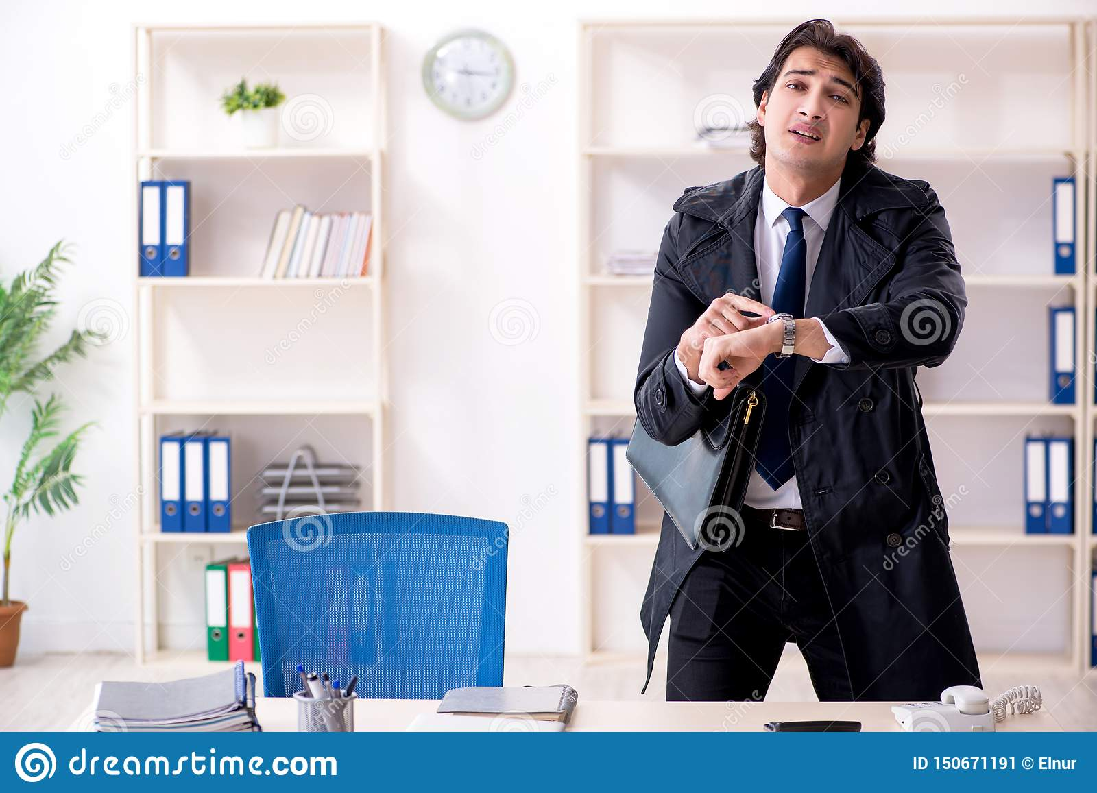 The young male employee in the office in time management concept