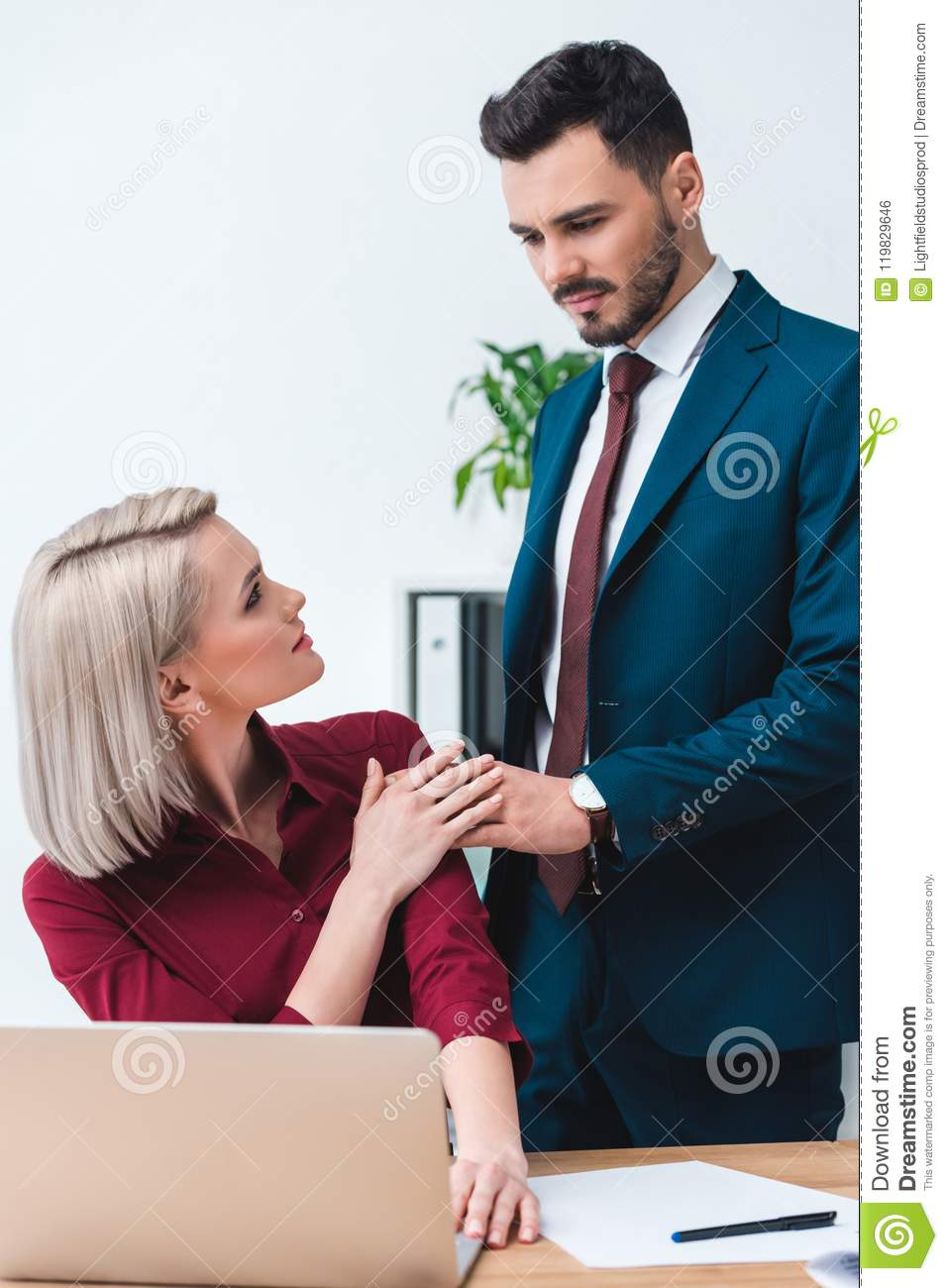 young male and female business colleagues holding hands and looking at each other