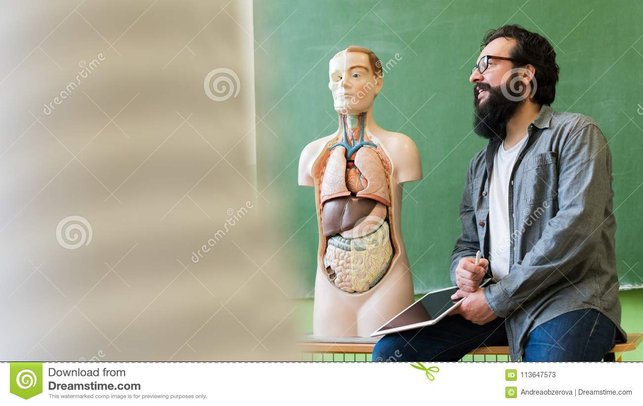 Young male hispanic teacher in biology class, holding digital tablet and teaching human body anatomy.