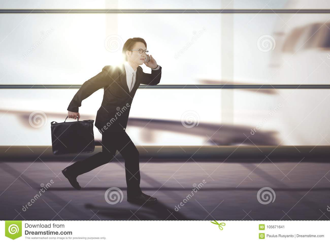 Male manager running on the airport terminal