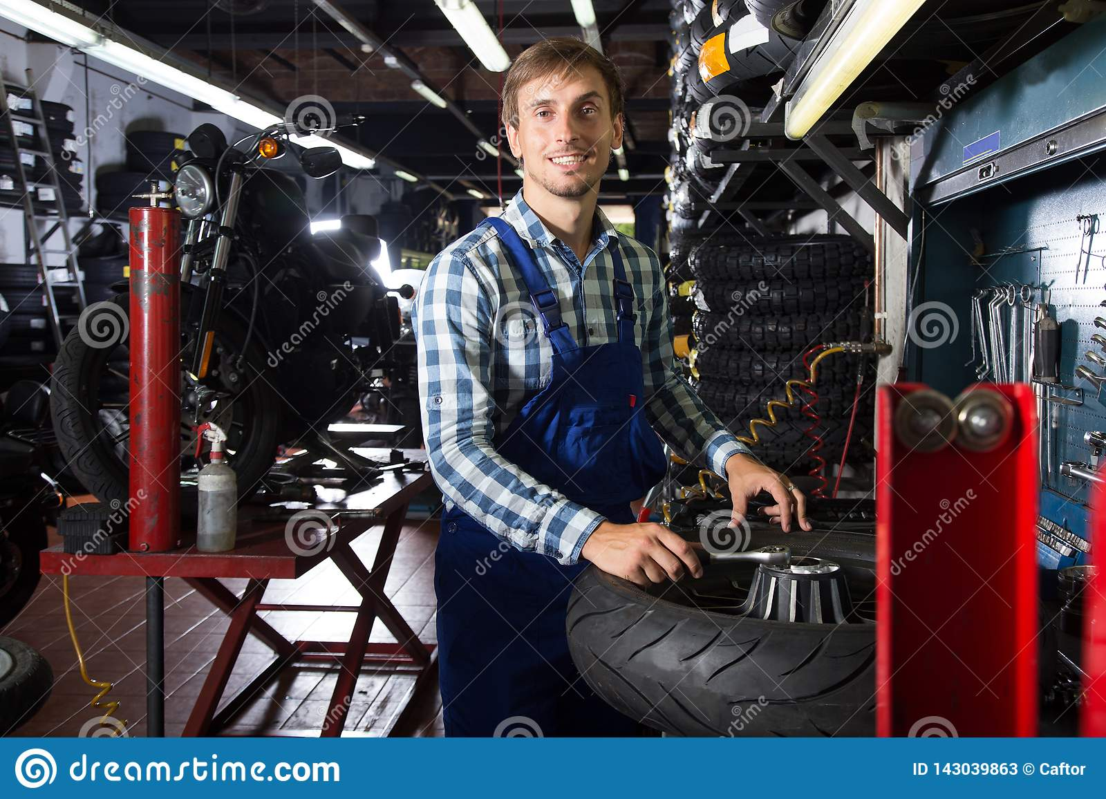 Young male mechanic working in auto repair shop