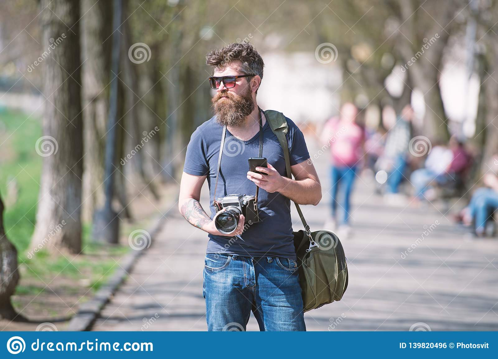Young male photographer stroll around city in search for perfect picture. Bearded man in stylish eyewear holding vintage