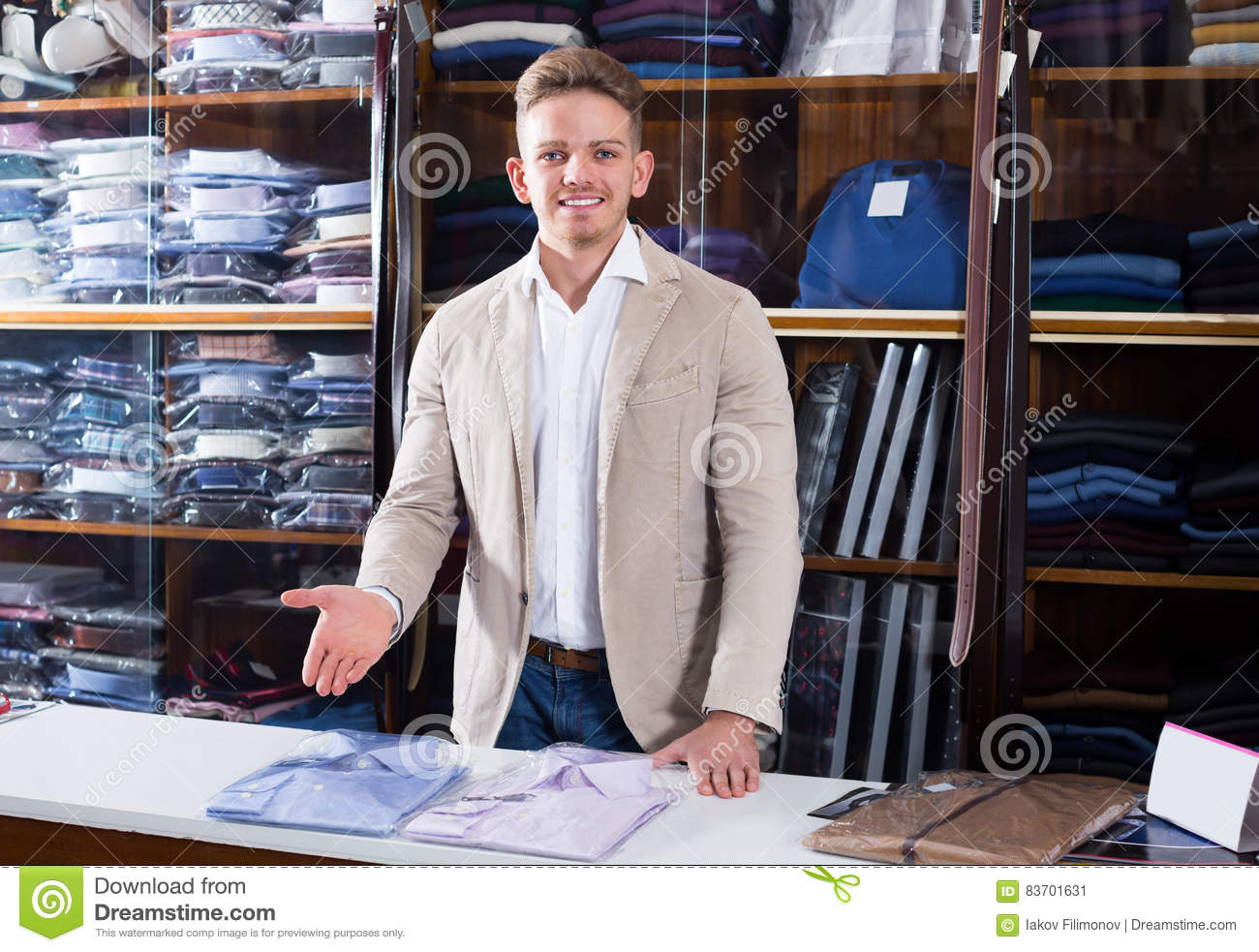 Young Male Shopping Assistant Offering Shirts Stock Photo