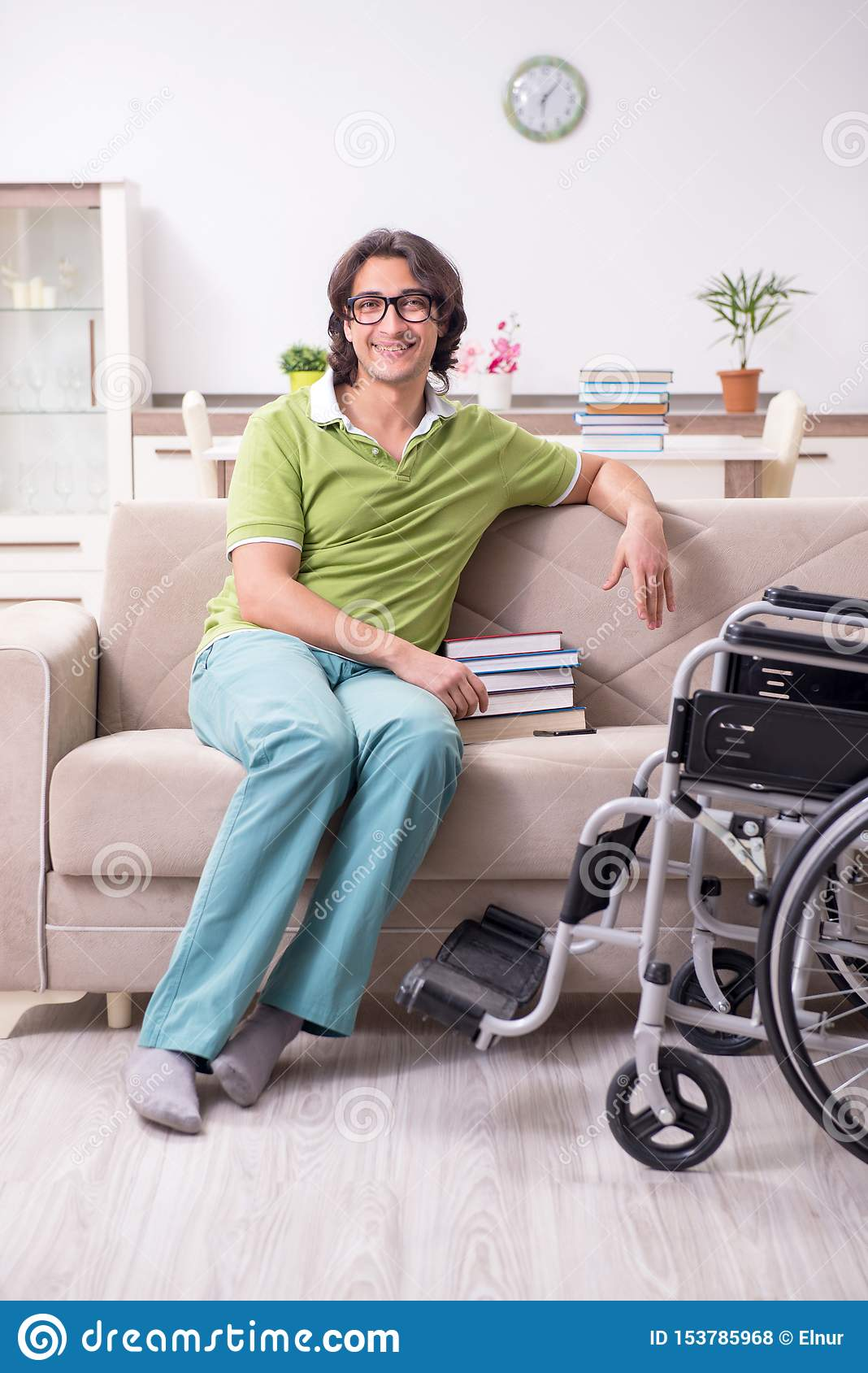 Young male student in wheelchair at home