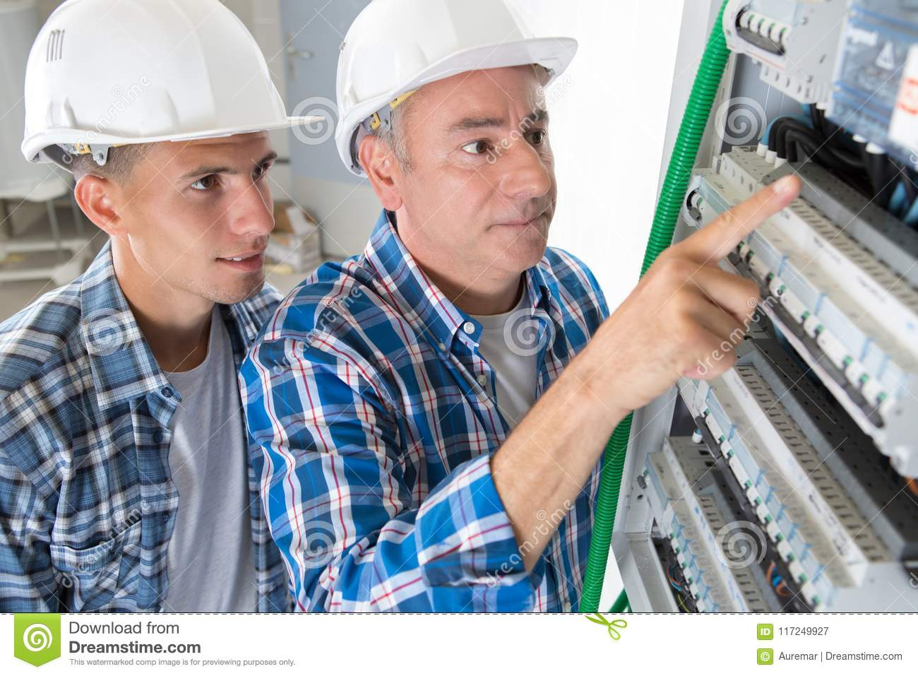 Young male technician learning to examine fusebox with multimeter probe
