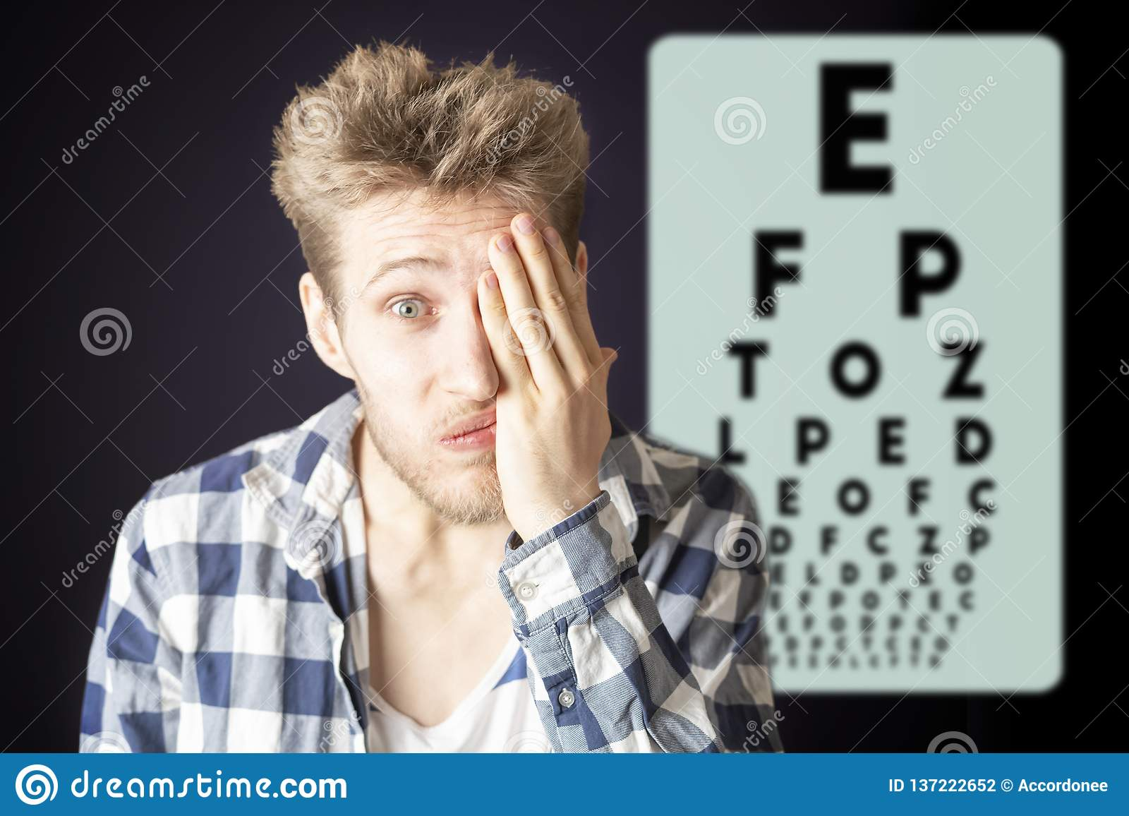 Young male test eye vision and cover eye with hand b