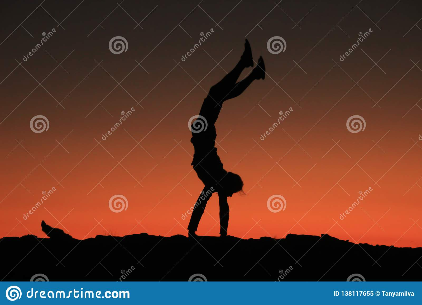 A young male traveler stands on his hands and performs acrobatic figures on a background of bright red with orange sky