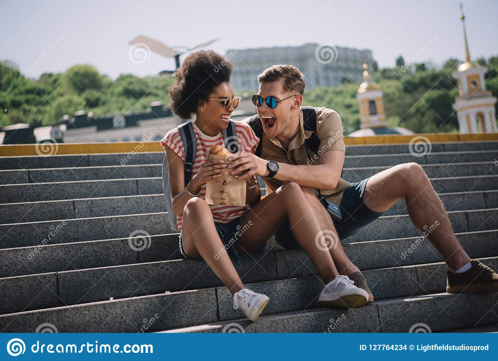 young male traveler trying to eat girlfriend