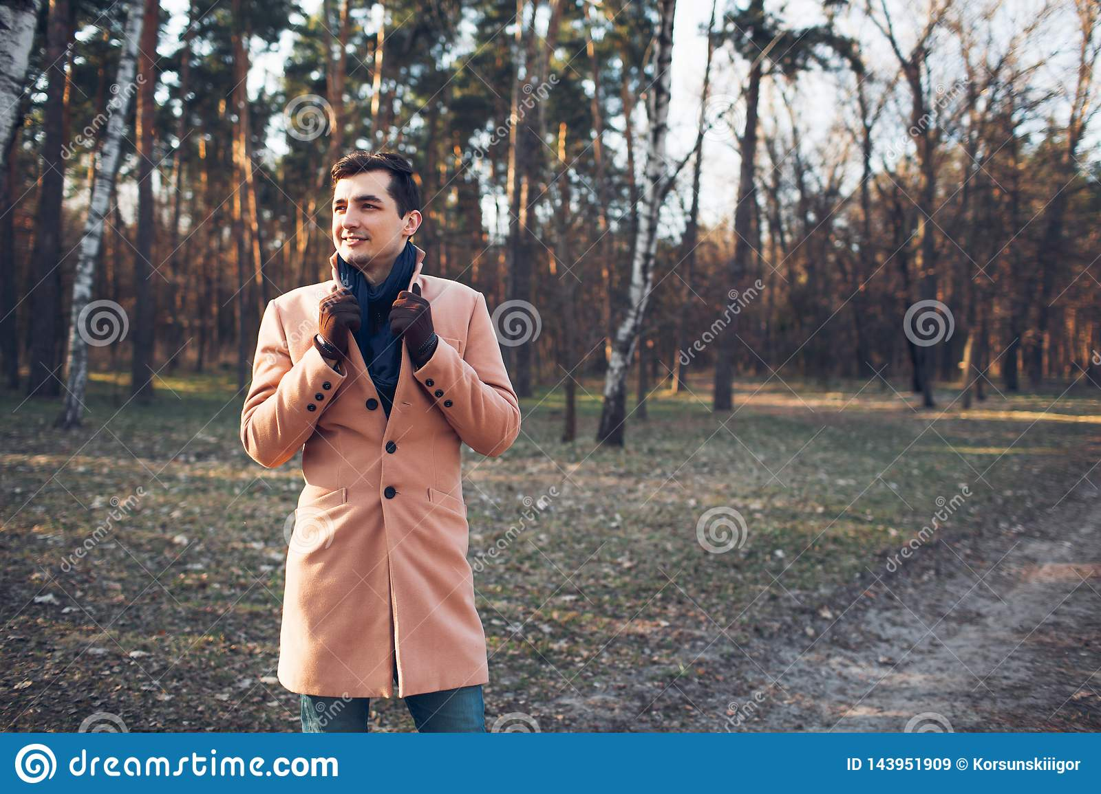 Young male walking in the forest in nature in a cream coat