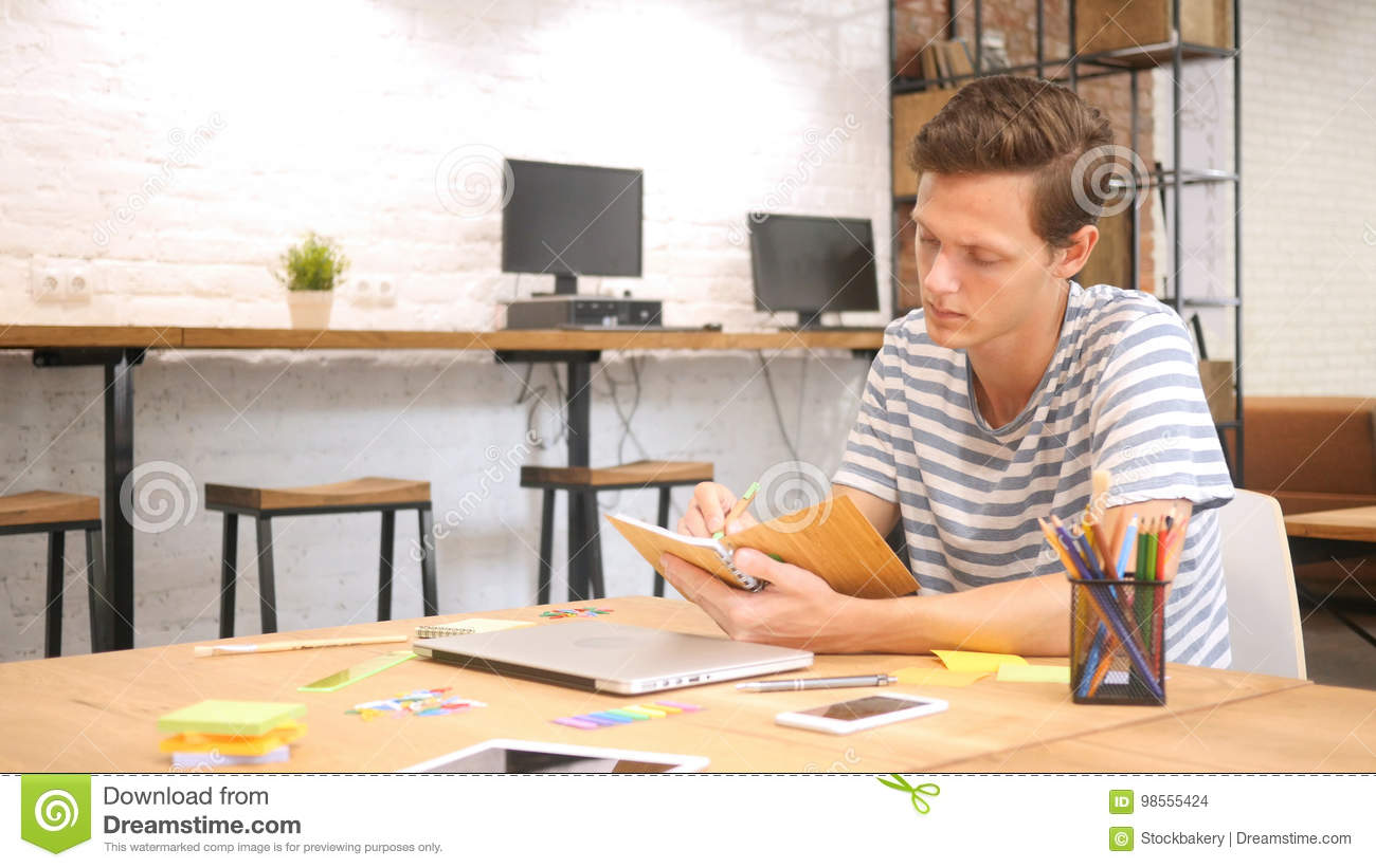 Young male writing in Notebook with Pen, Modern Loft Office