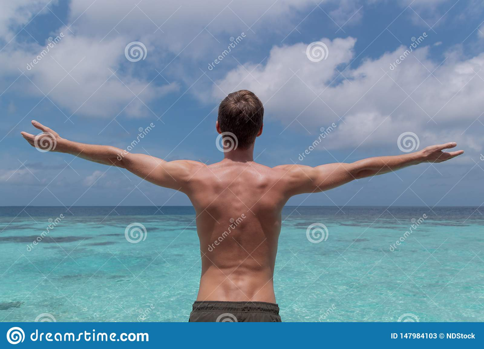 Young man with arms raised in front of clear blue water in a tropical holiday destination