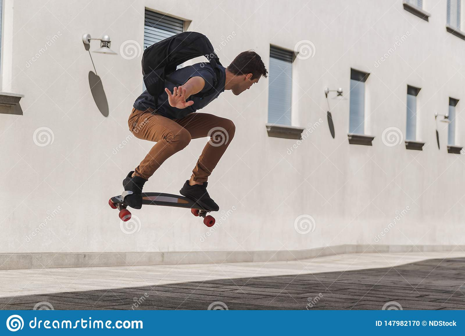 Young man with backpack using longboard and jumping when he is going to school after summer holidays
