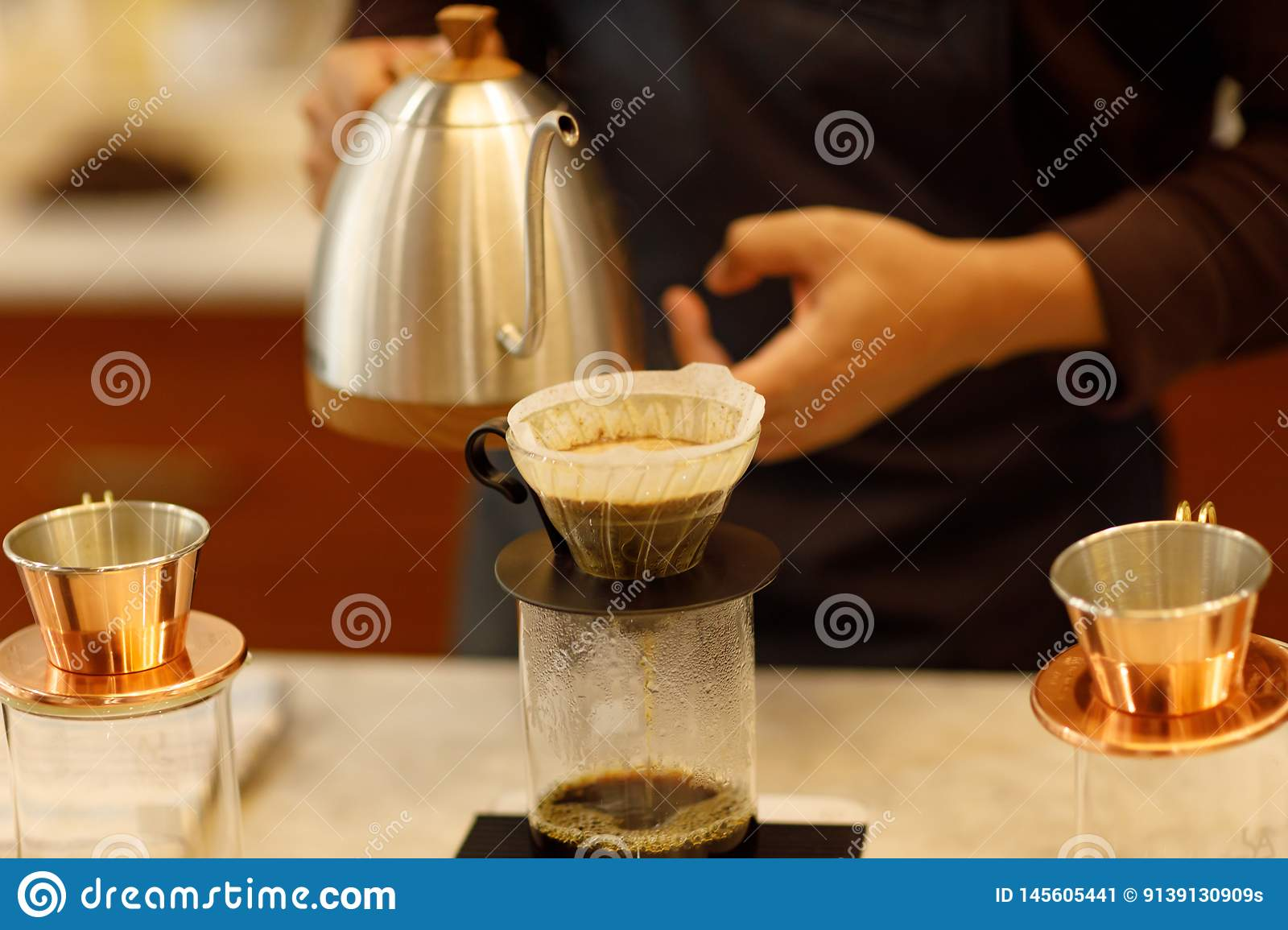 Young man barista pouring coffee