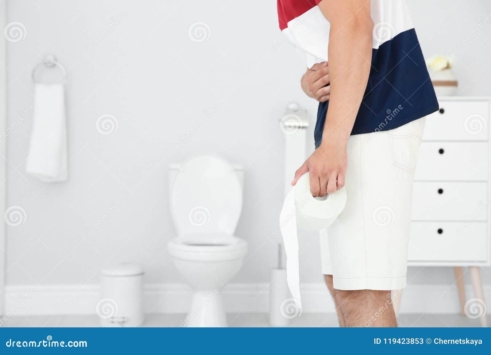 Peachy Young Man With Bath Tissue Standing Near Toilet Bowl Stock Creativecarmelina Interior Chair Design Creativecarmelinacom