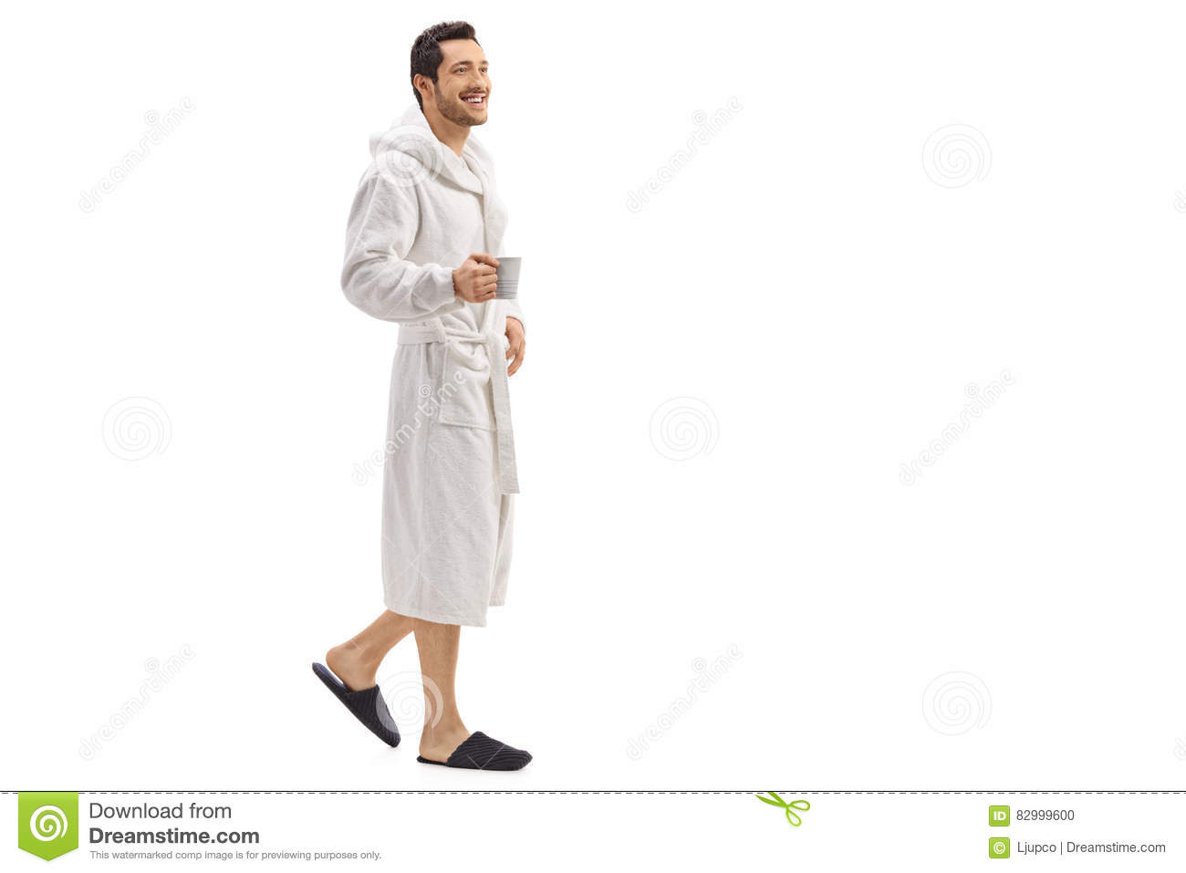 Young man in a bathrobe holding a cup and walking
