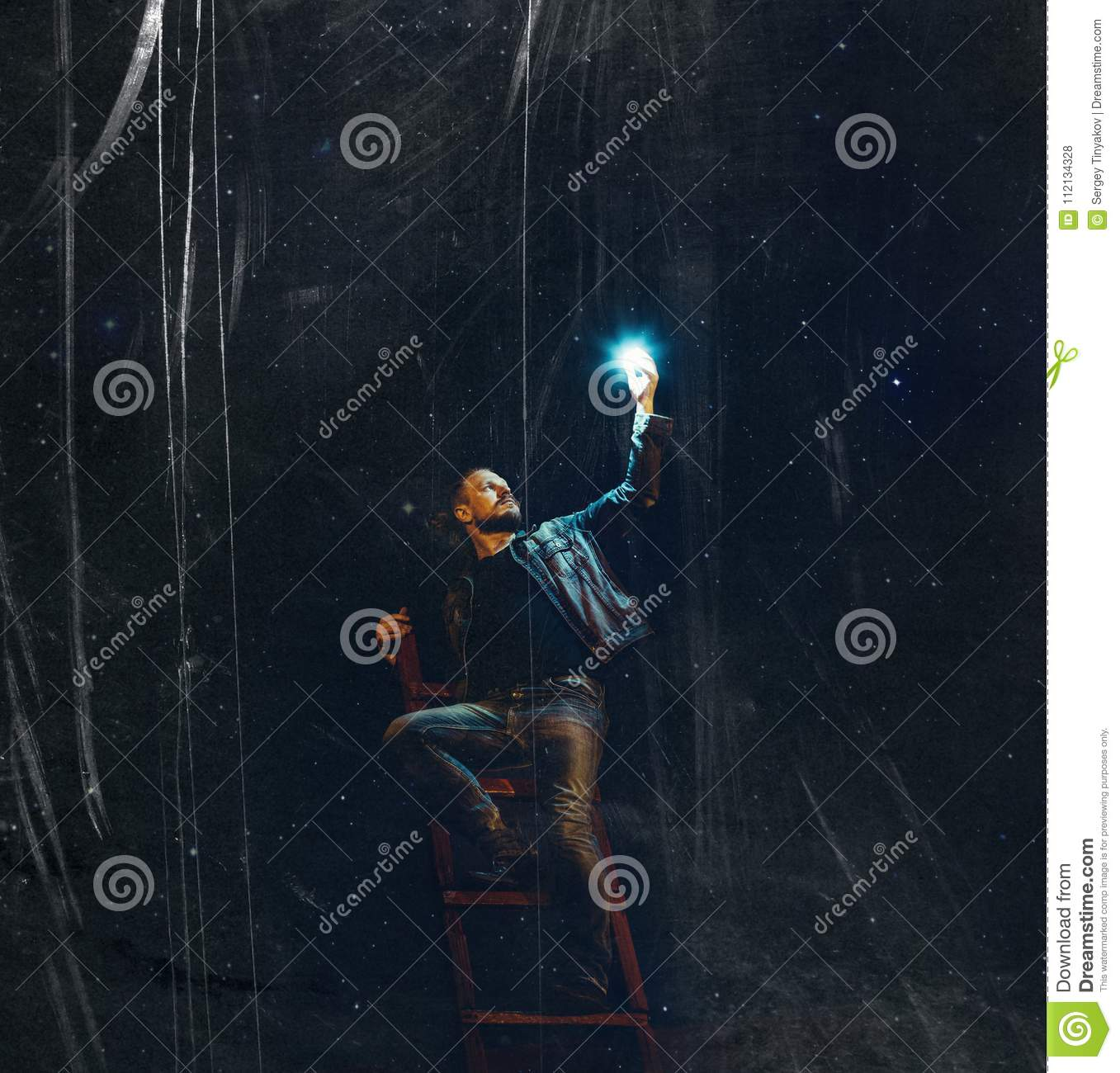 A young man with a beard on the stairs holds a star against the background of the night sky with scratches. creative concept