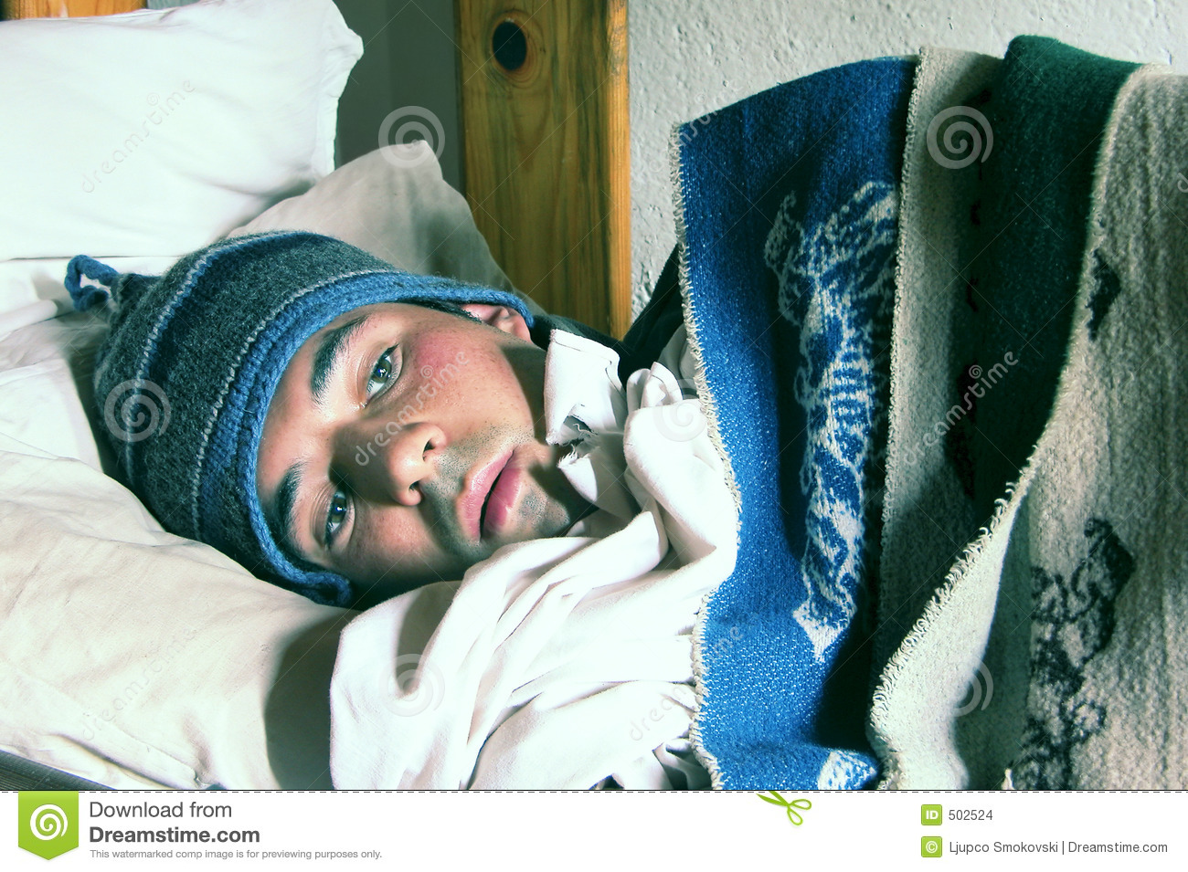 Young man in a bed feeling cold