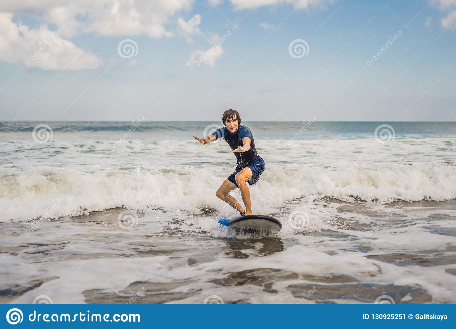 Young man, beginner Surfer learns to surf on a sea foam on the B