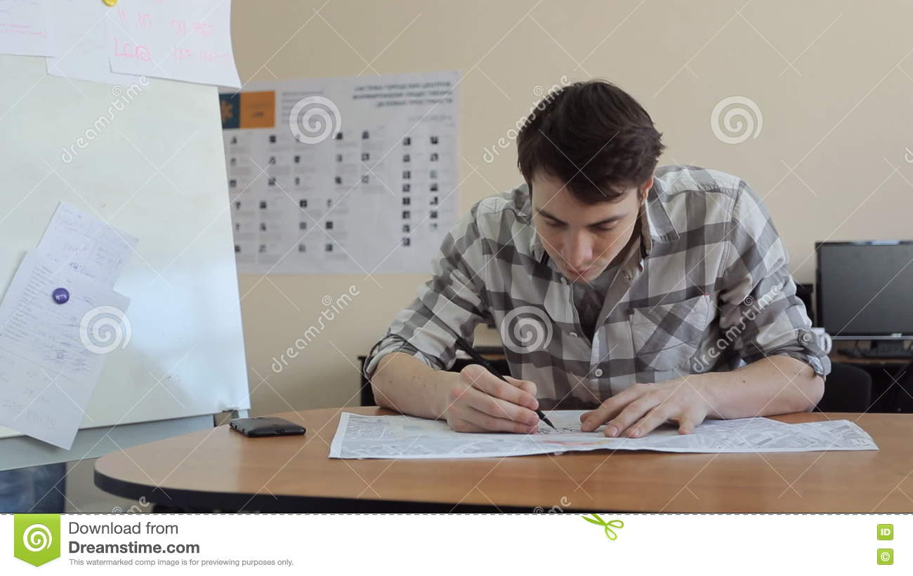 Young Man Bent Over Plan On Table And Draws On It With A Pen Sitting