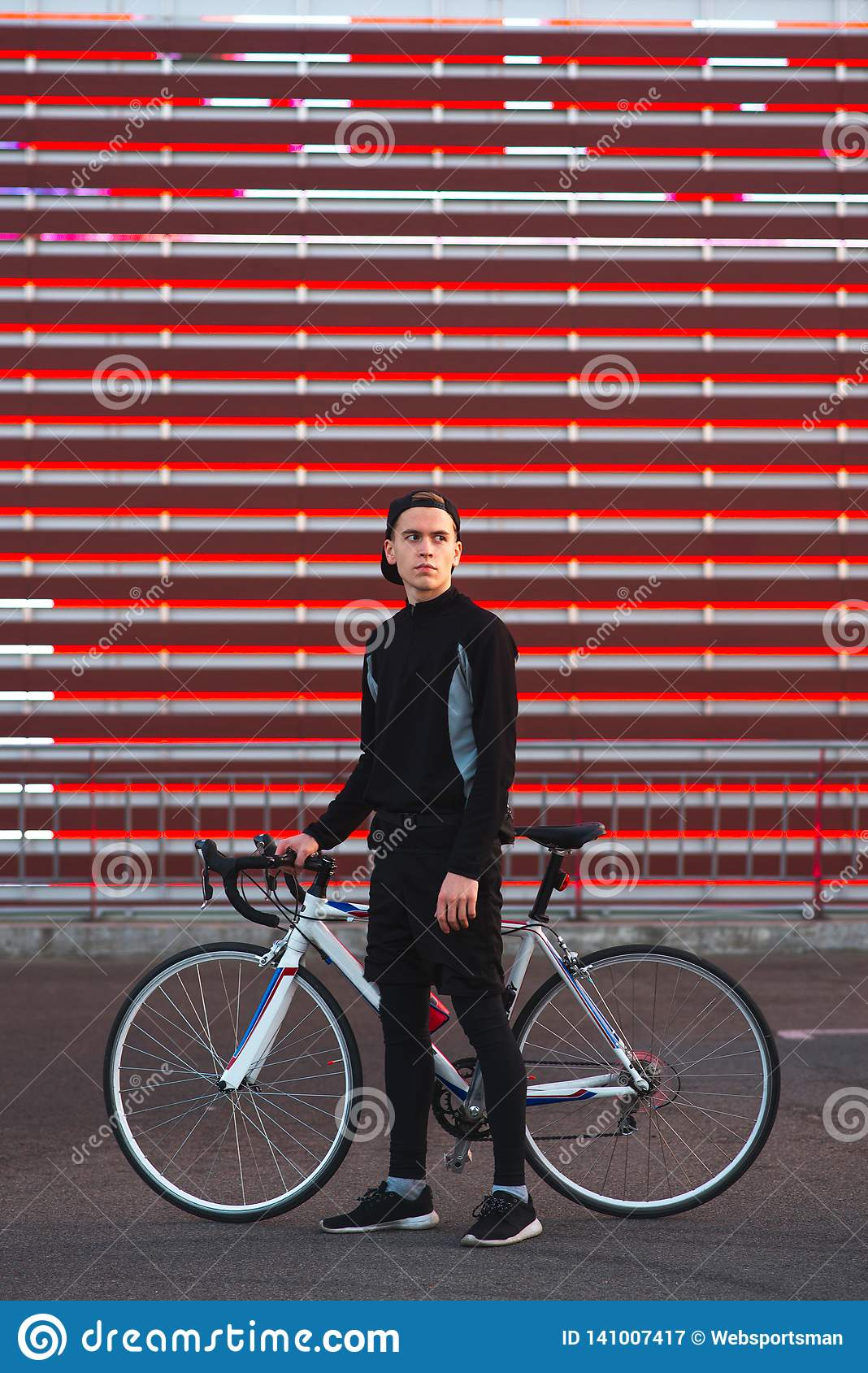 A young man with a bicycle and athletic dress is on an abstract red background