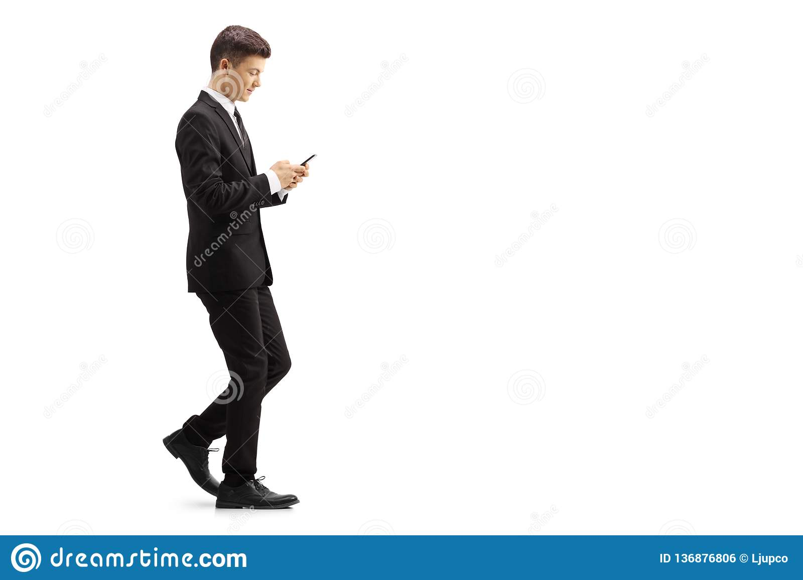 8618c014f7 Full length profile shot of a young man in a black suit walking and typing  onto a mobile phone isolated on white background