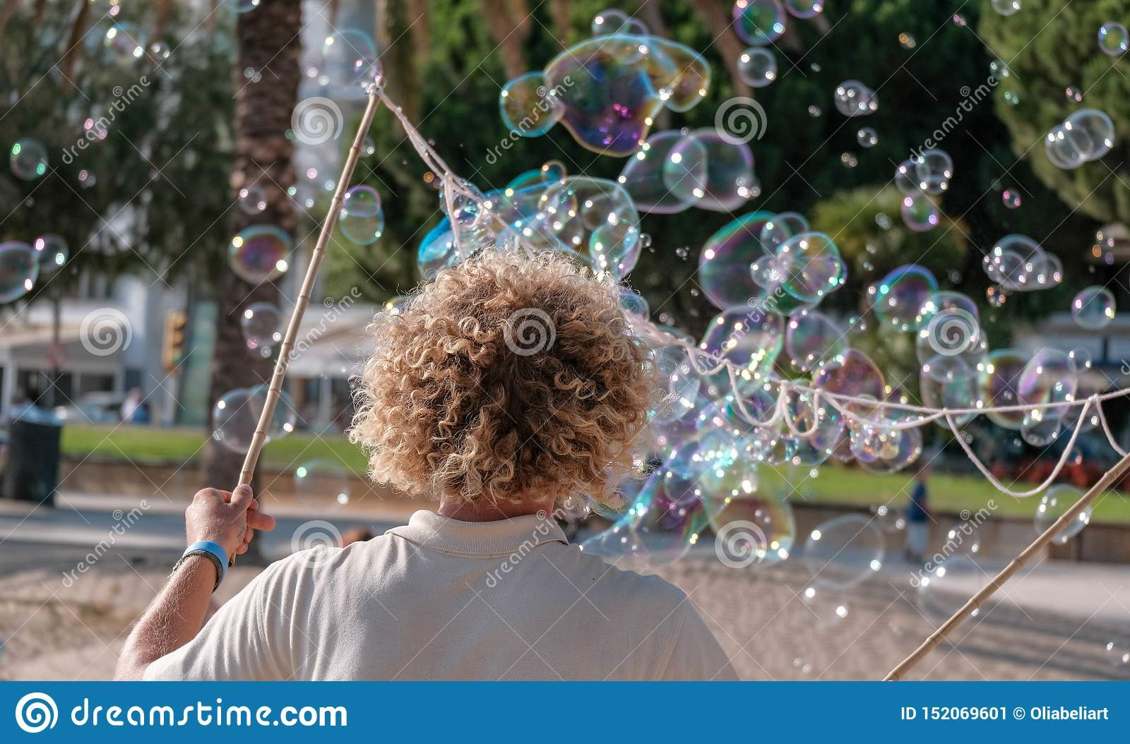 Young man blowing soap bubbles outdoor in summer time