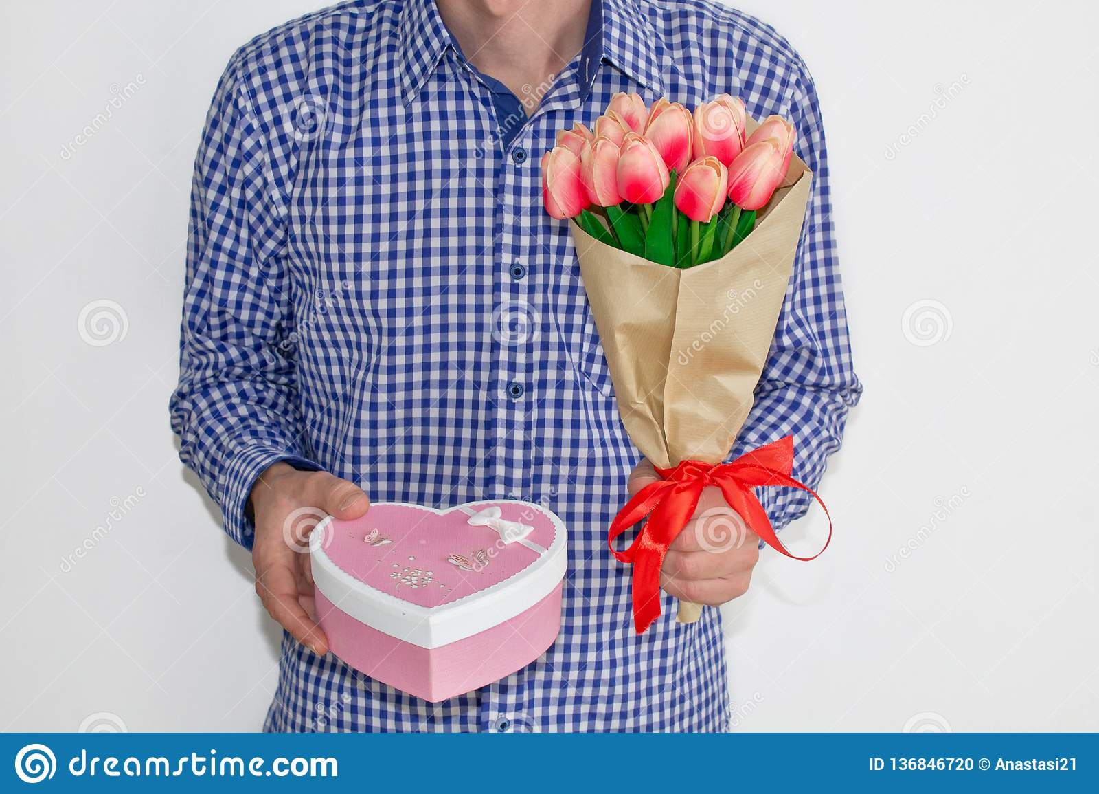 A young man in a blue plaid shirt and jeans, holding a bouquet of tulips and a gift box in the shape of a heart, on a white backgr