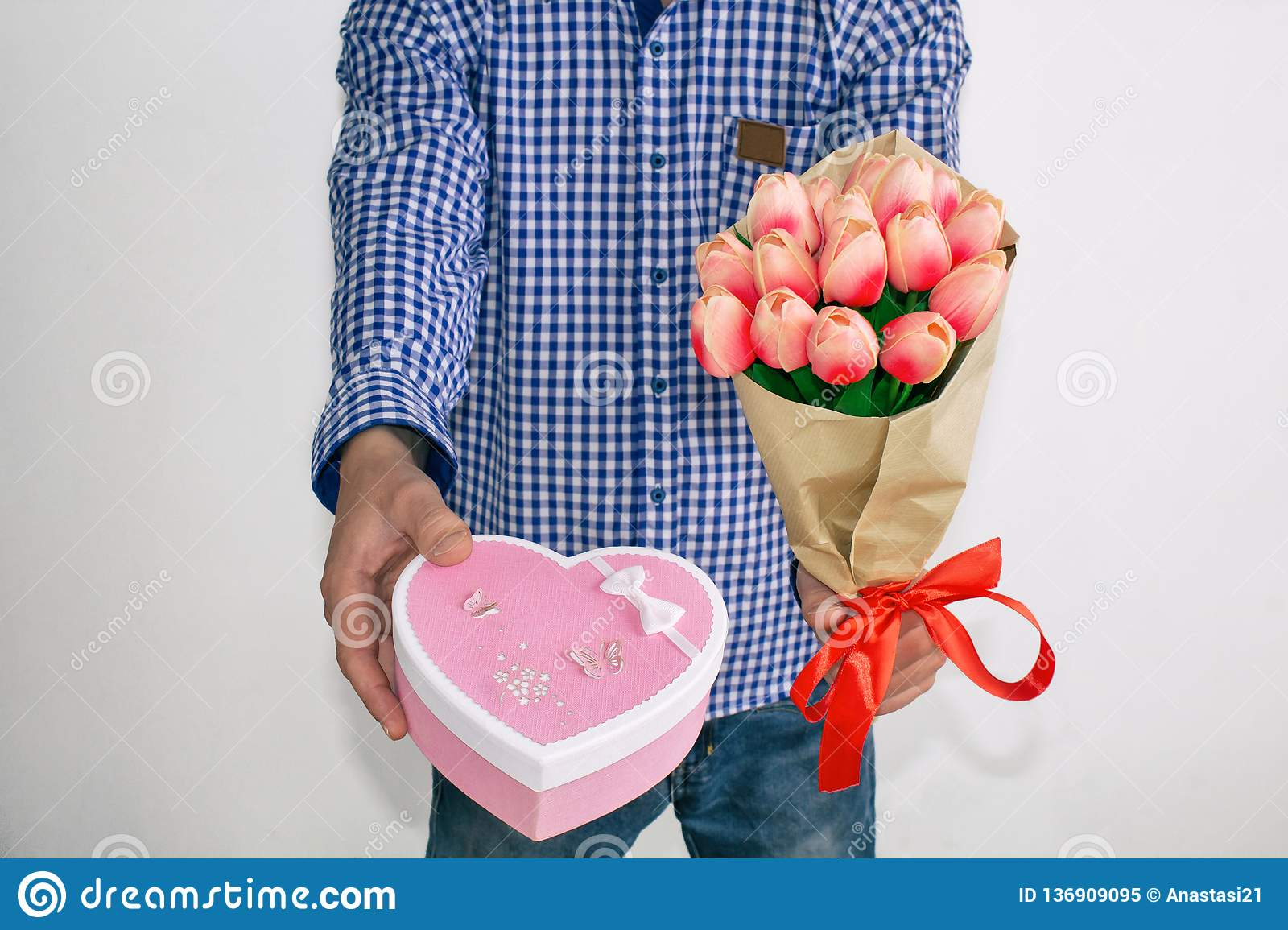 A young man in a blue plaid shirt and jeans, holding out a bouquet of tulips and a heart-shaped gift box, on a white background.