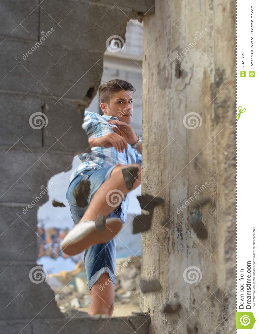Young man breaking through wall with a kick