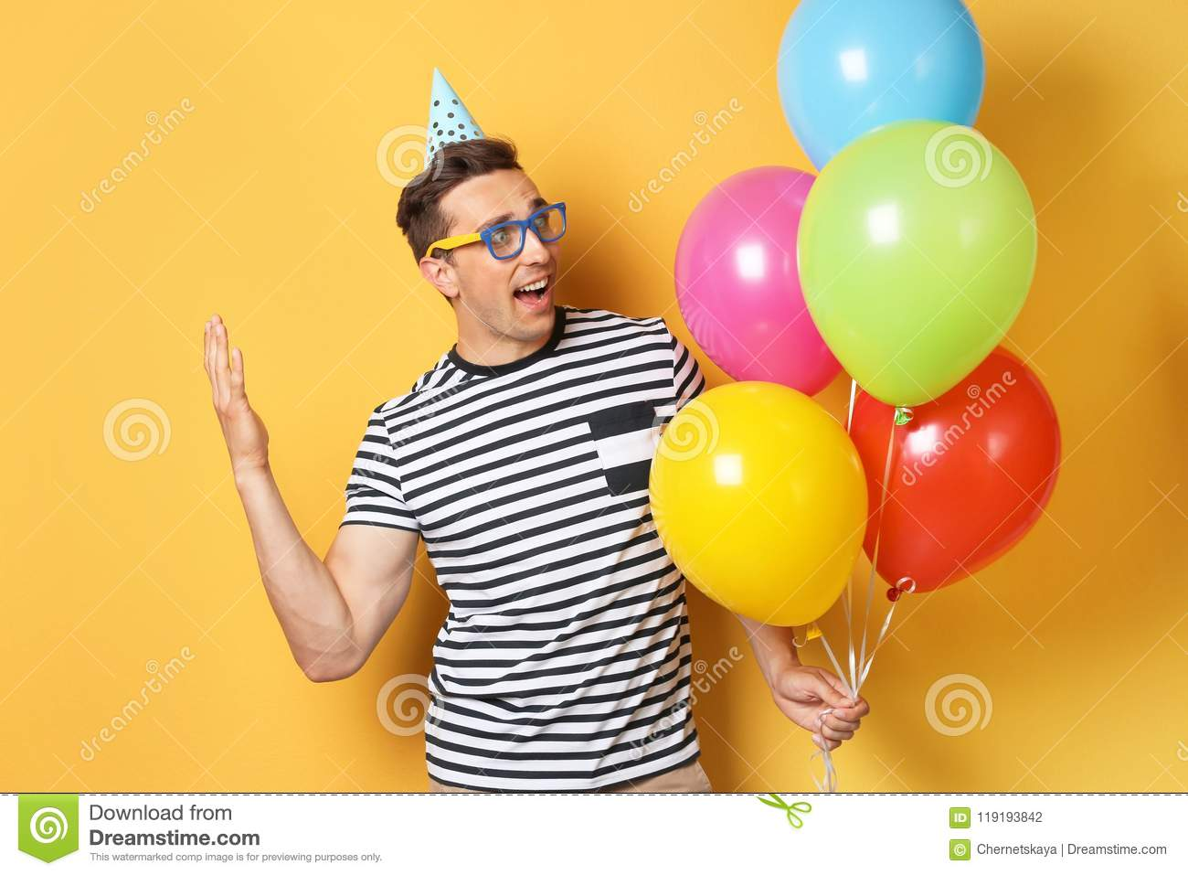 Young Excited Man With Bright Balloons On Color Background Birthday Celebration