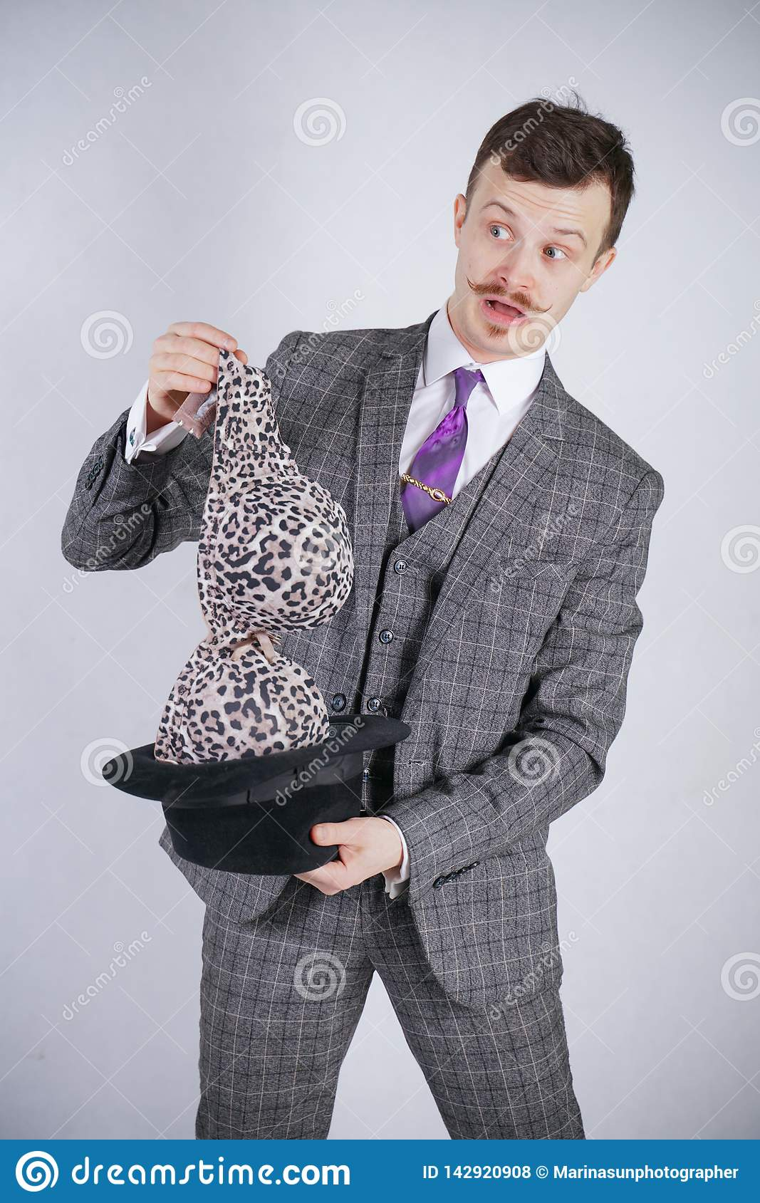 Young man in a business suit pulls out leopard bra from his hat, but he wanted tricks with wonder and wealth. emotional male feels