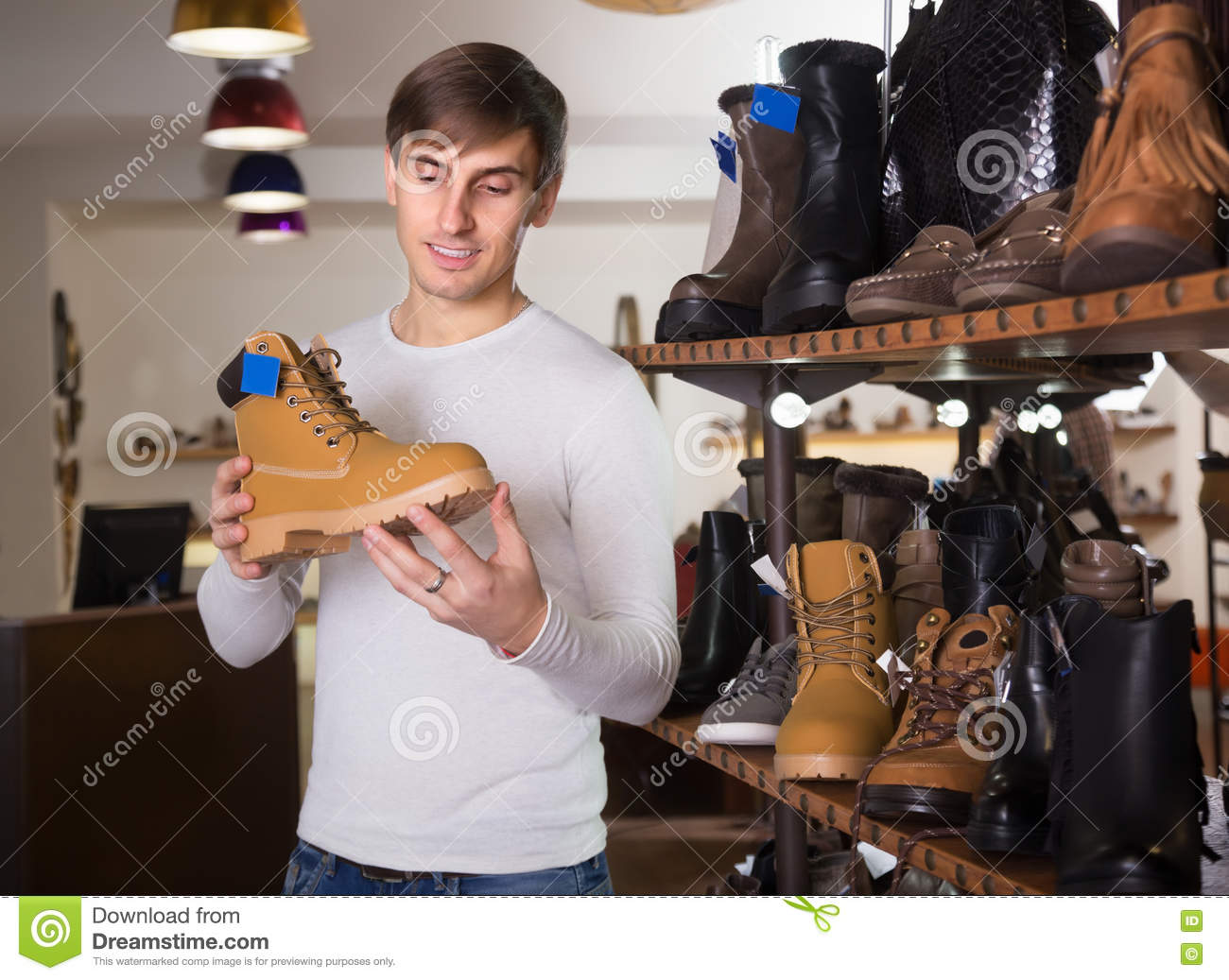 Young Man Buying Winter Shoes Stock