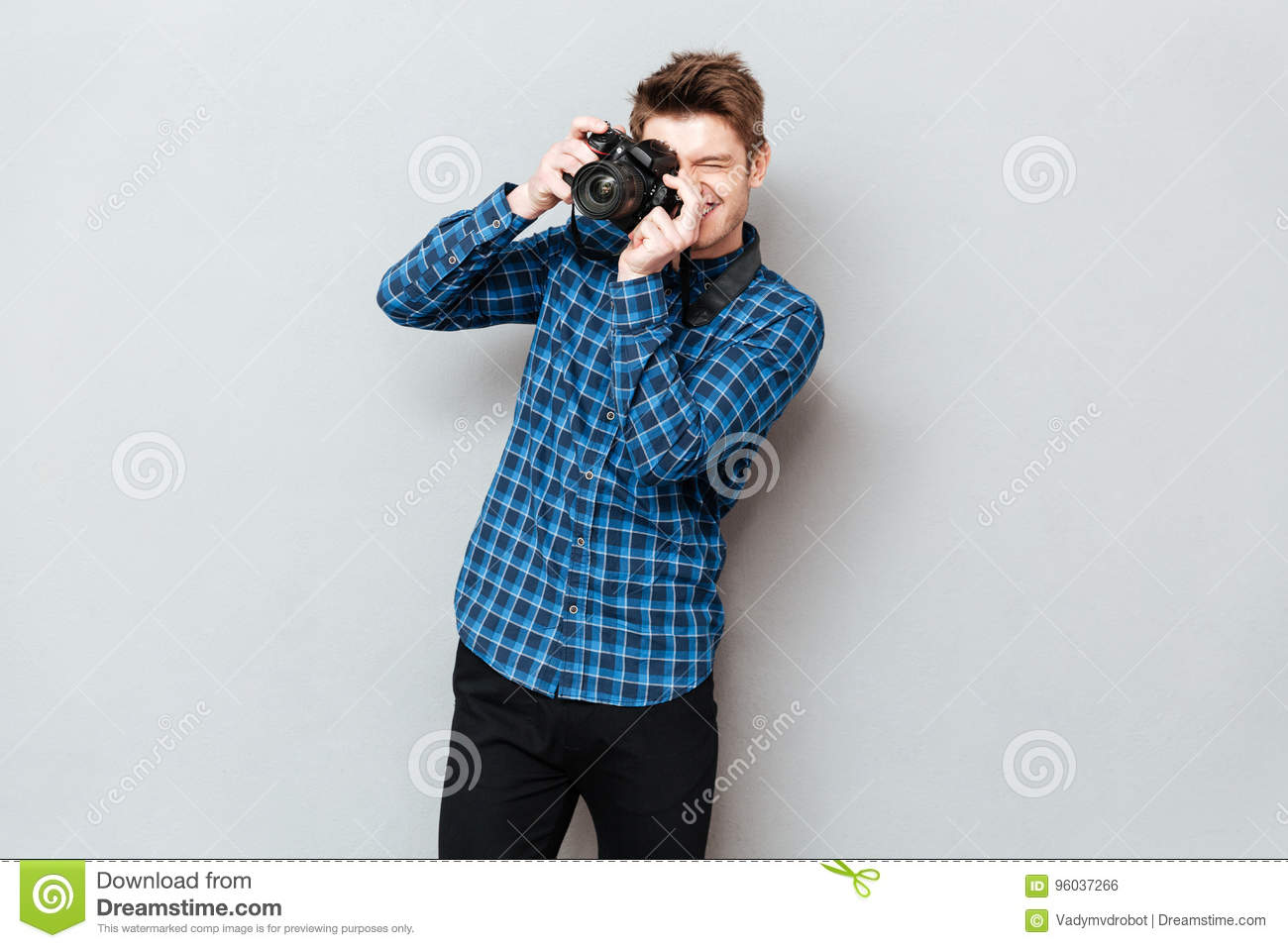 Young man with camera making photo